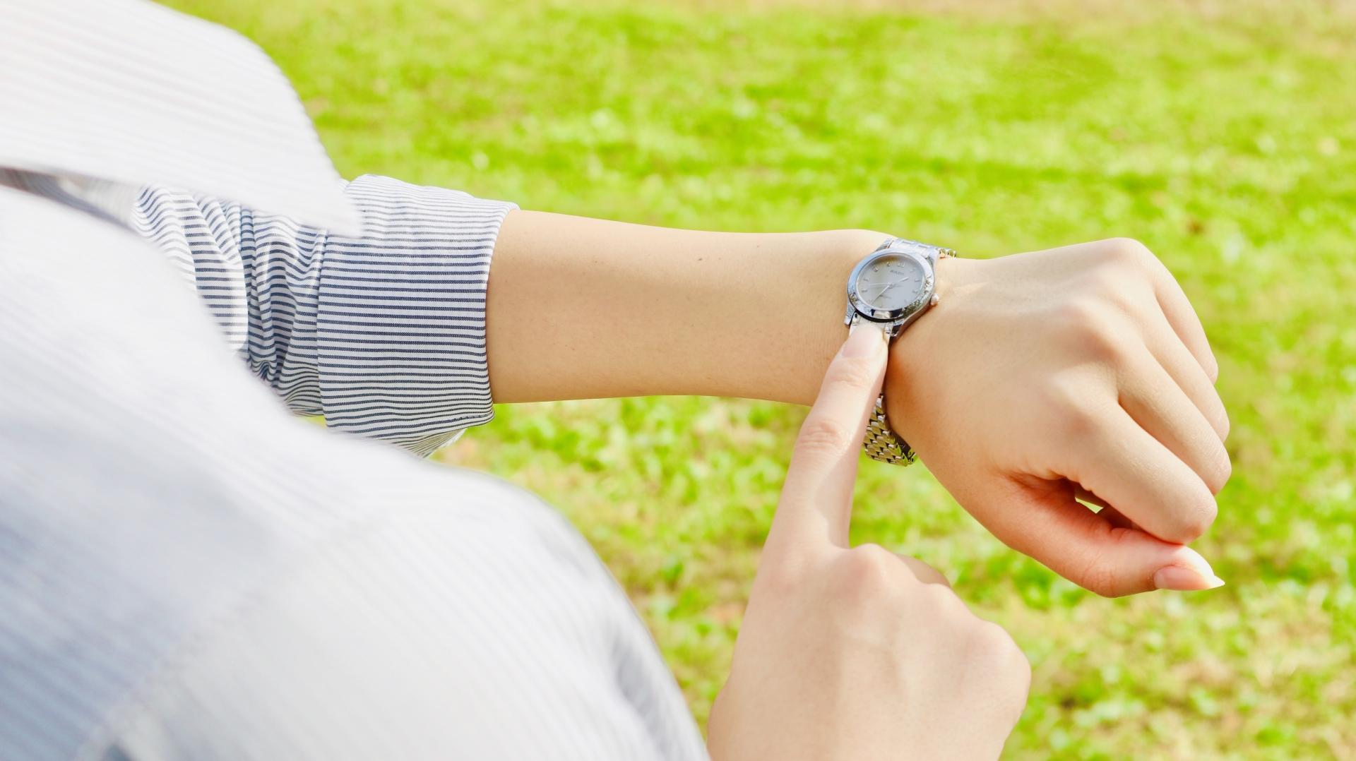腕時計を指さす女性
