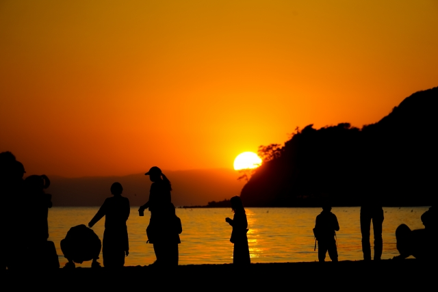 夕暮れの浜辺に立つ人々